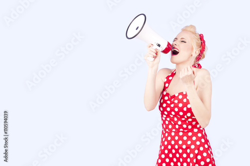 Fotografie, Obraz  Young woman holding megaphone, dressed in pin-up style red dress