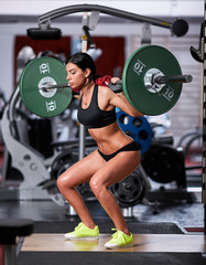 FototapetaWoman doing squats with barbell on neck