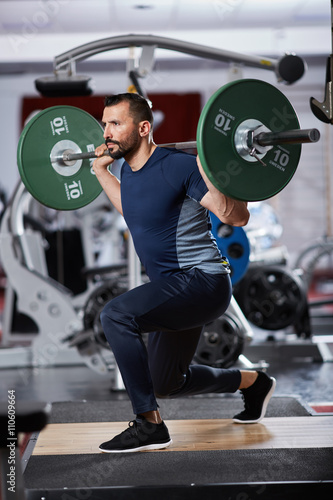 Man doing squats with barbell on neck - 110609664