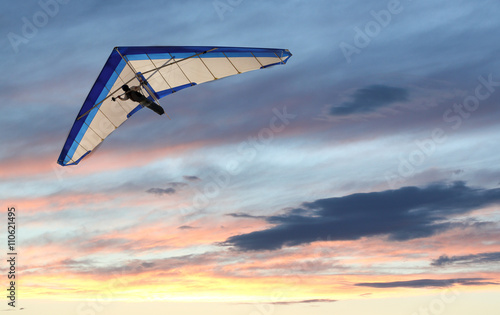 Foto op Plexiglas Luchtsport Hanglider - Hanglider Flying over the ocean at sunset