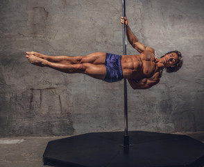 Shirtless man pole dancing.