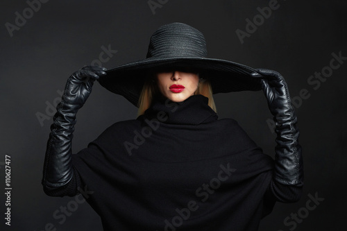 Photo  Beautiful woman in hat and leather gloves.halloween witch