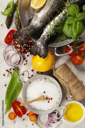 Foto  Raw rainbow trout with vegetables, herbs and spices