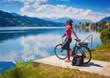 Leinwandbild Motiv woman with e-bike enjoying view over lake