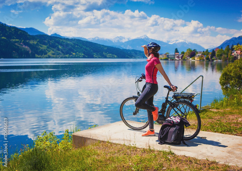 Plakat woman with e-bike enjoying view over lake