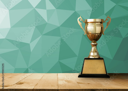Obraz na plátně golden trophy on wood table with vintage White Polygonal Mosaic