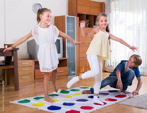 Children playing twister at home. Canvas-taulu