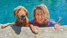 Funny Portrait Of Smiling Woman Playing With Dog And Training Golden Retriever Puppy In Blue Swimming Pool. Popular Dog Breeds, Outdoor Activity And Fun Games With Family Pet On Summer Beach Holiday.