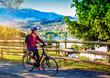 Leinwandbild Motiv woman with e-bike cycling beside a beautiful lake-lake and bike
