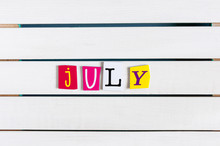 July Written With Color Magazine Letter Clippings On White Wooden Board. Summer Vacation Concept