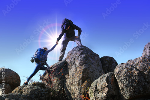 Fotografie, Obraz  Helping hands with sunlight between two climbers