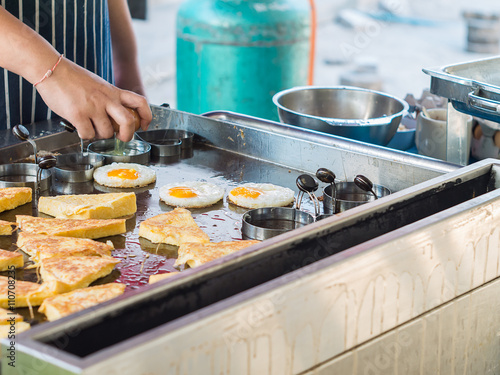 Aluminium Prints Buffet, Bar Chef cooking fried egg in shape form in hot pan
