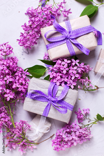 Wrapped gift boxes with presents and lilac flowers on grey tex