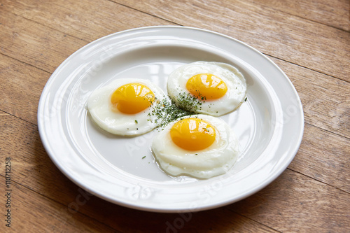 Tuinposter Gebakken Eieren Fried eggs in plate on table