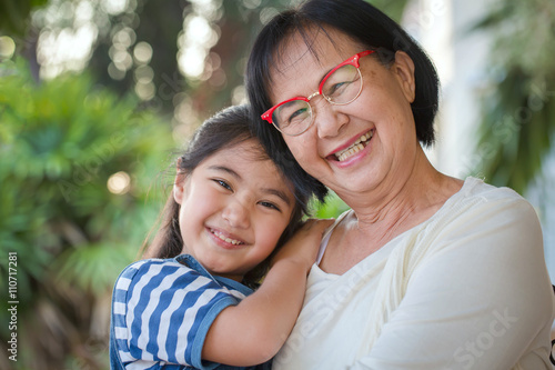 Fotografia  Happy little Asian girl hugging her grandmother