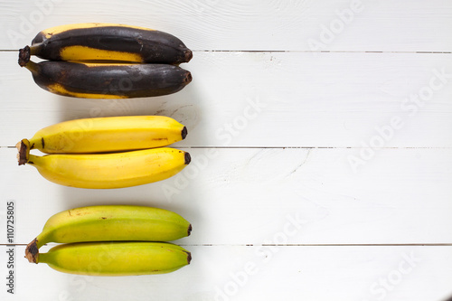 Valokuva  Green, yellow and black bananas arranged in a row on white wooden table