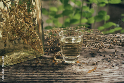 Wormwood drink in a small glass on rustic board