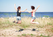 Two happy girls jumping on the beach