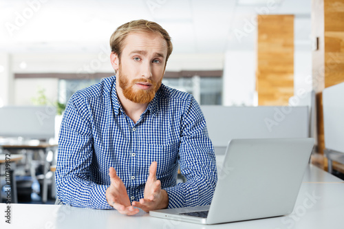 Serious businessman with laptop sitting and talking in office Canvas Print