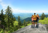 Family hiking on vacation, standing with arms around on top of the mountain, looking at beautiful summer mountains landscape. Blue sky in the background. Copy space. North Carolina, USA.