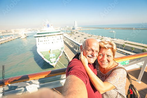 Tuinposter Schip Senior happy couple taking selfie on cruise ship travel at Barcelona harbour - Active retired people having fun