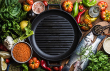 Ingredients For Cooking Healthy Dinner. Raw Uncooked Seabass Fish With Vegetables, Grains, Herbs And Spices Over Rustic Wooden Background, Cast Iron Pan In Center