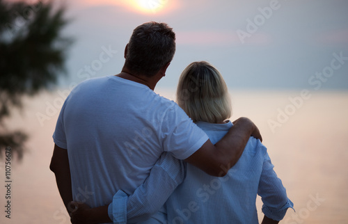 Obraz na plátně Romantic middle-aged couple standing arm in arm with their backs to the camera e