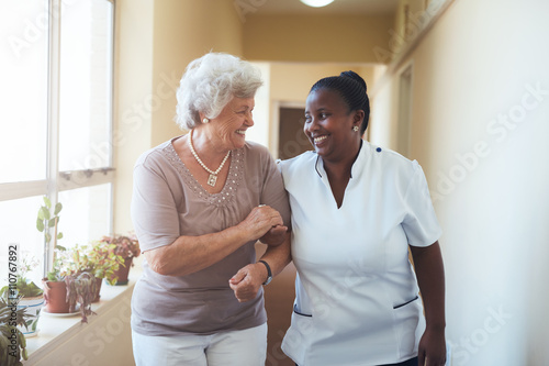 Photo  Smiling home caregiver and senior woman walking together