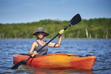 A Young Woman Paddling A Kayak