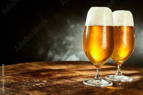 Two glasses full of beer on table