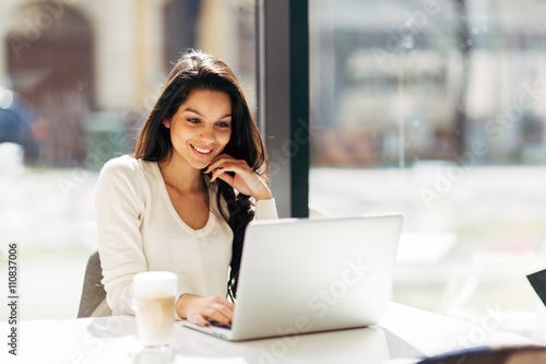 Photo  Brunette using laptop in cafe