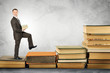 Businessman carries stack of books and walks up