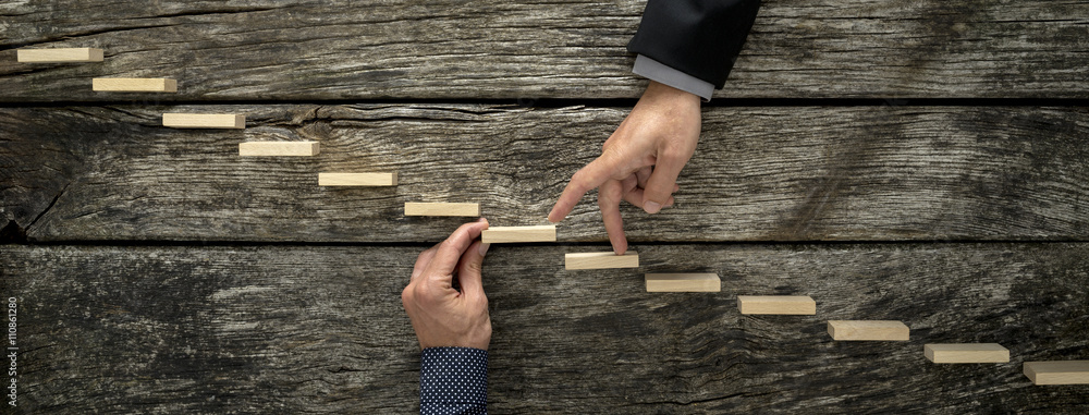 Fototapeta Hand of a businessman supporting a wooden step for his colleague
