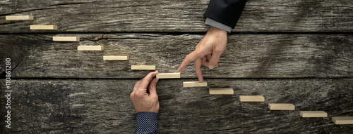 Fototapeta Hand of a businessman supporting a wooden step for his colleague obraz