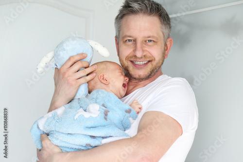 Fototapeta Młody tata z niemowlakiem na rękach uśmiecha się do kamery  obraz