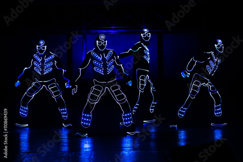 Montage in der Fensternische Karneval dancers in led suits on dark background, colored show