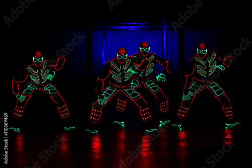 Photo sur Toile Carnaval dancers in led suits on dark background, colored show
