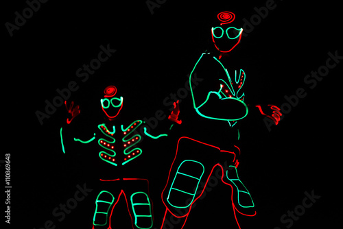 Papiers peints Carnaval dancers in led suits on dark background, colored show