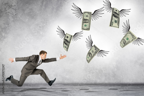 Photo Business man running to catch flying dollars