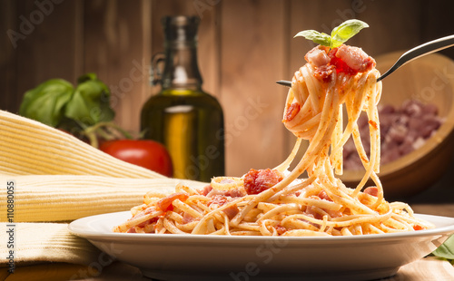 Fotografia spaghetti with amatriciana sauce in the dish on the wooden table