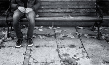 Lonely Man Sits On A Wooden Bench In The Park With Tree Leaves On The Ground. Single Young Man With Personal Problems. Black And White Color Effect Used.