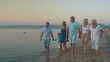 Steadicam shot of parents, grandparents and child walking barefoot along the coast in the evening. Woman taking mobile shot of her big happy family