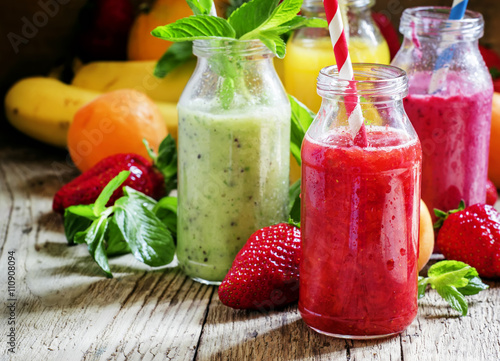 Crédence de cuisine en verre imprimé Jus, Sirop Multi-colored bottles with fresh fruit smoothies with striped st