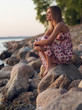 Beautiful young girl sitting on the rocky shore in a dress and looking at the sunset