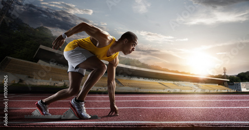 Foto  Sport. Sprinter leaving starting blocks on the running track.