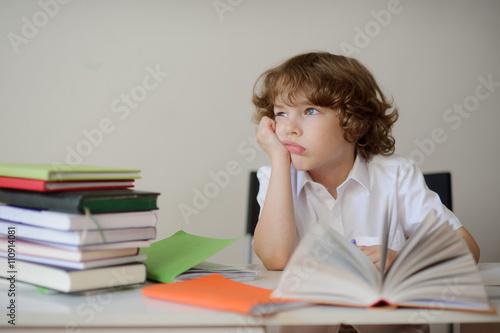 Fotografie, Obraz  Daydreaming schoolboy sits at a school desk