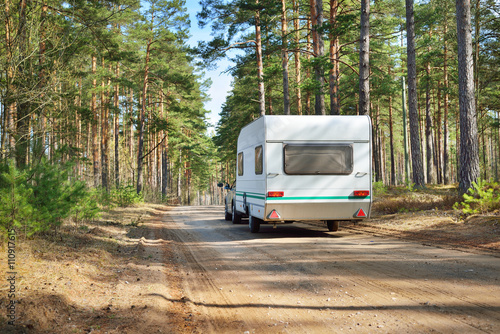Photo Caravan trailer on a forest road, on a sunny spring day