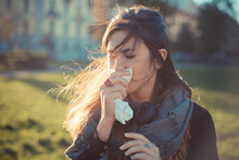 Mid Adult Woman Blowing Nose With Handkerchief In Park