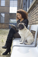 Portrait Of Pug Dog Sitting On Chair With Young Woman In Office Courtyard