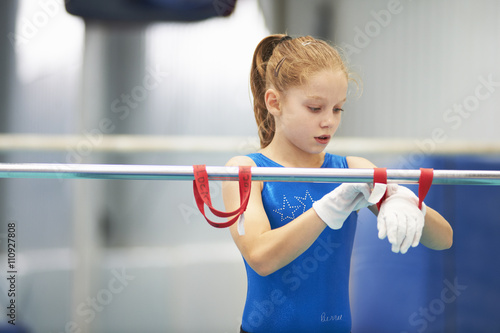 Young gymnast using training wrist straps to aid practise on bars Poster